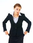 Roke-young-caucasian-woman-in-business-attire-holding-her-empty-pockets-that-are-turned-out-and-looking-at-the-viewer-with-a-shocked-expression-by-yuri-arcurs